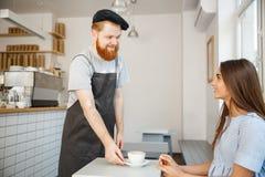 Concept d'affaires de café - serveur ou barman servant le café chaud et parlant avec la belle dame caucasienne dans la robe bleue photographie stock