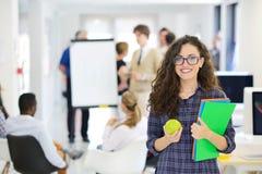 Concept d'affaires, de démarrage et de personnes - équipe créative heureuse avec l'ordinateur et dossier dans le bureau Photographie stock libre de droits