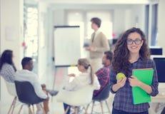 Concept d'affaires, de démarrage et de personnes - équipe créative heureuse avec l'ordinateur et dossier dans le bureau Photos stock