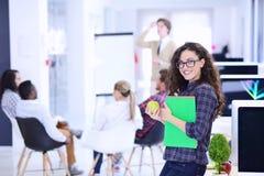 Concept d'affaires, de démarrage et de personnes - équipe créative heureuse avec l'ordinateur et dossier dans le bureau Photo libre de droits