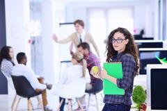 Concept d'affaires, de démarrage et de personnes - équipe créative heureuse avec l'ordinateur et dossier dans le bureau Photos libres de droits