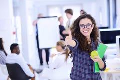 Concept d'affaires, de démarrage et de personnes - équipe créative heureuse avec l'ordinateur et dossier dans le bureau Image libre de droits