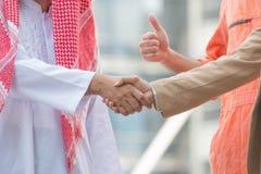 Concept d'affaires et de bureau - l'Arabe et l'homme d'affaires secouent Image stock
