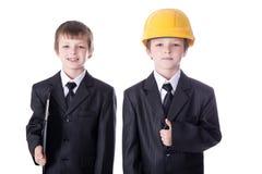 Concept d'affaires et de construction - deux petits garçons dans les affaires Photographie stock libre de droits