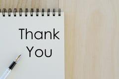 Concept d'affaires et de finances La vue supérieure du stylo et le carnet écrit avec vous remercient sur le fond en bois L'espace photographie stock libre de droits