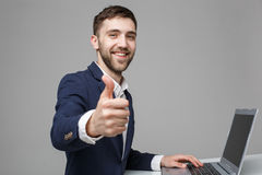 Concept d'affaires - homme bel d'affaires de portrait montrant le coup et le visage sûr de sourire devant son ordinateur portable Photographie stock