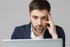 Concept d'affaires - homme sérieux bel d'affaires de portrait dans le costume regardant l'ordinateur portable Fond blanc Images stock