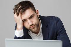 Concept d'affaires - homme sérieux bel d'affaires de portrait dans le costume regardant l'ordinateur portable Fond blanc Photographie stock