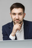 Concept d'affaires - homme sérieux bel d'affaires de portrait dans le costume regardant le travail dans l'ordinateur portable Fon Images stock