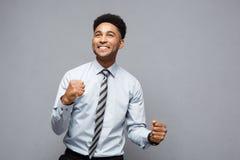 Concept d'affaires - le jeune Afro-américain heureux sûr jetant des poings en air célébrant pour le succès projette Photos libres de droits