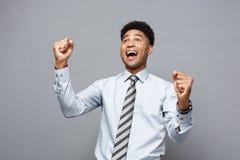 Concept d'affaires - le jeune Afro-américain heureux sûr jetant des poings en air célébrant pour le succès projette Image stock
