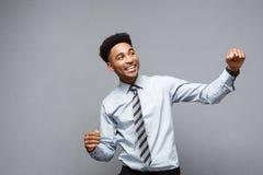 Concept d'affaires - le jeune Afro-américain heureux sûr jetant des poings en air célébrant pour le succès projette Photo libre de droits