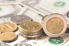 Concept d'affaires Les euro pièces de monnaie se ferment sur les billets de banque américains d'argent liquide du dollar Images libres de droits