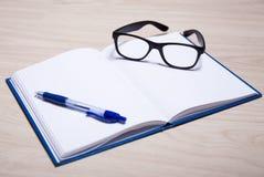 Concept d'affaires ou d'éducation - carnet, stylo et verres Image stock