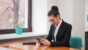 Concept d'affaires Une femme dans des écouteurs regardant son téléphone banque de vidéos