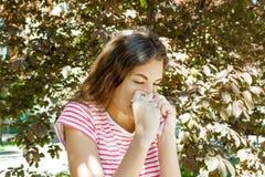 Concept d'allergie Jeune fille de éternuement avec l'essuie-glace de nez parmi les arbres de floraison en parc image stock