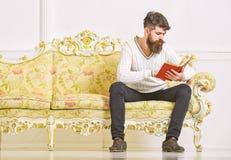 Concept d'amélioration d'individu Macho sur le livre de lecture concentré de visage Livre de lecture de type avec l'attention Hom photos stock