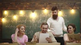 Concept d'ami Groupe d'?tudiants ?tudiant ensemble dans une salle de classe Groupe d'étudiante des quatre jeunes avec le professe banque de vidéos