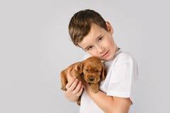 Concept d'amitié d'animal familier d'enfants - petit garçon avec le chiot rouge d'isolement sur le fond blanc Image stock