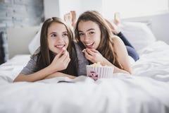Concept d'amitié, de personnes, de partie de pyjama, de divertissement et de nourriture industrielle Photos stock