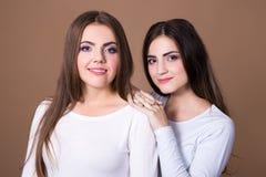 Concept d'amitié - portrait de deux filles au-dessus de beige Photographie stock