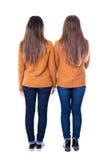 Concept d'amitié - vue arrière de deux filles se tenant d'isolement dessus Photo stock