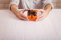 Concept d'amour Équipez tenir le cadeau orange avec le ruban noir dans des mains Jour du `s de femmes Jour du ` s de St Valenine Photographie stock libre de droits