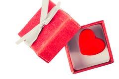 Concept d'amour Coeur rouge décoratif dans le boîte-cadeau rouge intéressant d'isolement sur le blanc Photographie stock