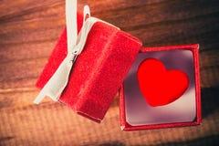 Concept d'amour Coeur rouge décoratif dans le boîte-cadeau rouge intéressant sur le fond en bois Photo libre de droits