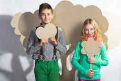 Concept d'amour Couples des enfants Garçon et fille tenant un coeur de carton Images libres de droits