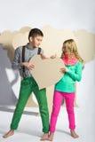 Concept d'amour Couples des enfants Garçon et fille tenant un coeur de carton Photos libres de droits
