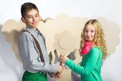 Concept d'amour Couples des enfants le garçon donne à une fille des fleurs de carton Image stock