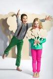 Concept d'amour Couples des enfants le garçon donne à une fille des fleurs de carton Photo stock