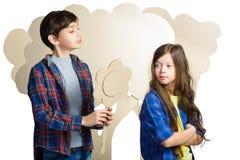 Concept d'amour Couples des enfants le garçon donne un isolat de fleurs de carton de fille sur le blanc Photographie stock libre de droits