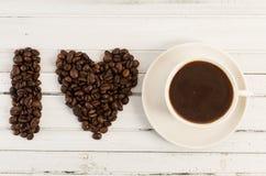 Concept d'amour de café avec la forme de foyer faite de haricots Photographie stock
