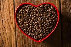 Concept d'amour de café Grains de café au coeur dans le bown Image stock