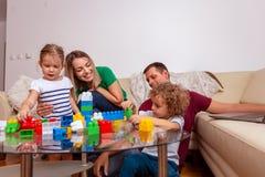 Concept d'amour de famille - Homme et femme de sourire jouant avec des enfants à la maison images stock