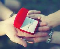 Concept d'amour, de fiançailles et de mariage - les mains couplent tenir l'anneau Image libre de droits