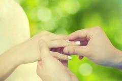Concept d'amour, de fiançailles et de mariage - main et femelle masculines avec l'anneau Image stock