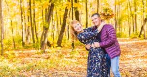 Concept d'amour, de relations, de famille et de personnes - couple de sourire ayant l'amusement dans le parc d'automne Images libres de droits