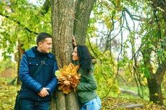 Concept d'amour, de relations, de famille et de personnes - les couples de sourire étreignant en automne se garent Photos stock