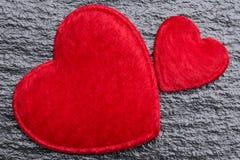 Concept d'amour : Deux coeurs pelucheux rouges au-dessus de fond noir approximatif d'ardoise Photo libre de droits
