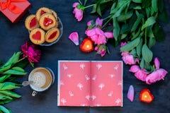 Concept d'amour et de soin Composition romantique en style - carnet ouvert entouré avec des pivoines, biscuits, tasse avec du caf Photo stock
