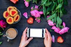 Concept d'amour et de soin Mains femelles jugeant le smartphone entouré avec des pivoines, des biscuits et la tasse avec du café, Photographie stock libre de droits