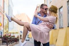 Concept d'amour et de voyage - jeune homme tenant son amie dans l'ha Photographie stock libre de droits