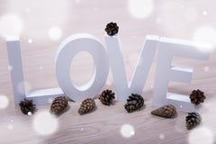 Concept d'amour et d'hiver - lettres et cônes en bois de pin avec le sno Photographie stock libre de droits