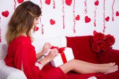 Concept d'amour - femme magnifique dans le boîte-cadeau rouge d'ouverture de robe dans d Photos stock