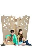 Concept d'amour Garçon élégant et fille s'asseyant sur le fond de la ville de carton blanc d'isolat Images stock