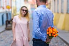 Concept d'amour - jeune homme donnant des fleurs à son amie Images stock