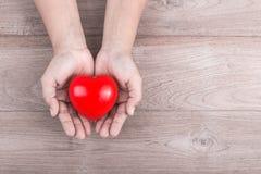 Concept d'amour : La femme remet tenir le coeur rouge sur l'étiquette en bois brune Photos stock